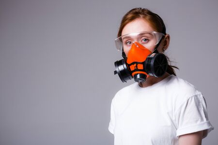 Beautiful red-haired girl in white T-shirt stands in mask respirator and safety glasses and looks at camera on a gray background