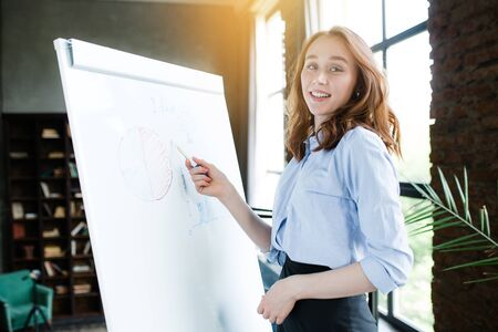 The red-haired girl makes a presentation and shows the drawn graphics on the blackboard. Presentation with light on the background.