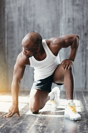 Sports shooting of a muscular dark-skinned trainer in a white T-shirt crouched in a pose to start running in the gym.