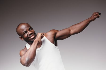 Portrait of a Black Pilates Trainer showing studio dance movement Dabbing