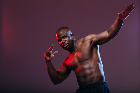 African sports man with embossed torso makes a dance movement Dab. The body is highlighted in red neon.