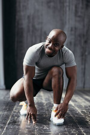 A strong and muscular smiling African American in white cross-country squatted after playing sports and looking at the camera.