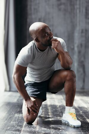 Profile view of a sporty African American in a gray t-shirt and black shorts, squatting down and holding his hand at his mouth 免版税图像