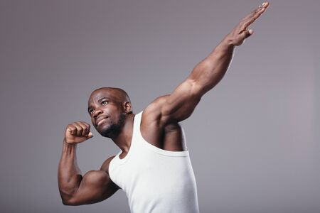 Portrait Muscular male bodybuilder in white T-shirt and sports shorts demonstrates his muscles by stretching his arm up in studio