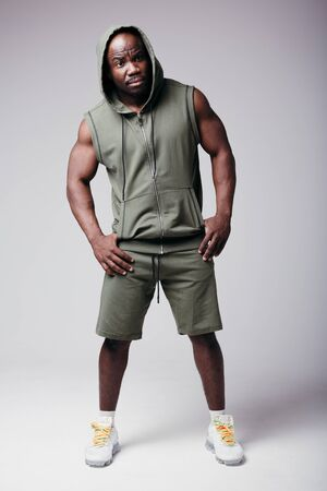 A muscular male bodybuilder in a tracksuit stands on a light background and looks at the camera, demonstrating his arms are full. 스톡 콘텐츠