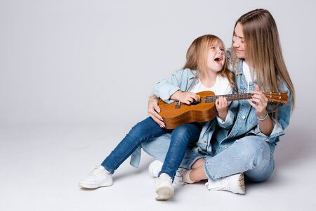 Charming Caucasian girl sings songs to her mother with a guitar. The daughter sits on the lap of the parent and enjoys the music.