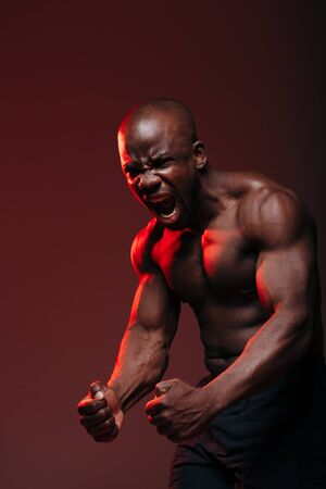 Sports shot with a red light of a dark-skinned muscular bodybuilder showing naked torso muscles and screaming