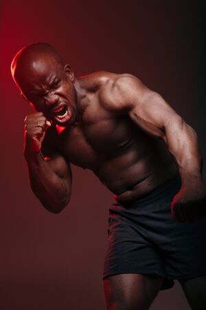 Vertical photo Muscular fighter frenchman standing in a boxing pose doing a punch towards the camera in red light.