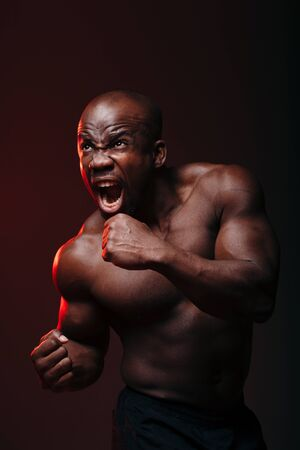 A dark-skinned, naked-chested boxer issues a cry before the fight in red neon light in the studio Standard-Bild