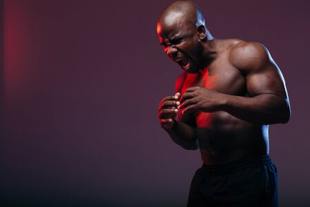 Muscular Frenchman bodybuilder holds his hands to his chest and emits a fighting cry in a neon light in the studio Archivio Fotografico