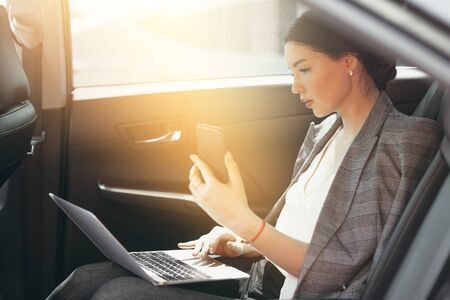 Beautiful woman in a business suit sits in the passenger compartment and checks data through a smartphone and laptop