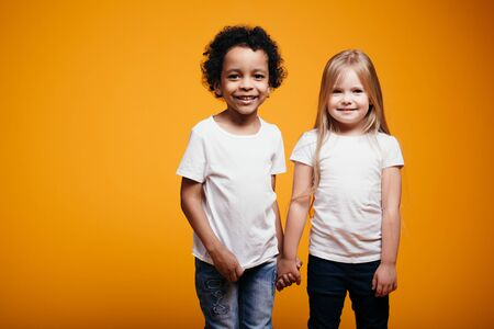 Portrait of two young children in the studio. A dark-skinned boy and a blonde girl are posing for the camera on an orange background in the studio.