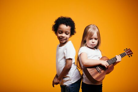 Perky African American boy dancing next to a European girl playing ukulele on a guitar and bothering her