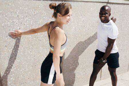Two trainers of different nationalities are doing exercises on turns of the body leaning their hands against wall on the street.