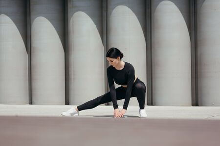 Athletic girl in a black tight-fitting suit does side squats for stretching the muscles of the hips and quadriceps Banque d'images