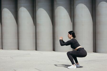Profile of a Pilates trainer in a black sports uniform doing squats on the street against the background of concrete cylinders.