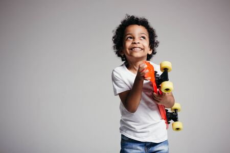 A dark-skinned curly boy in a white T-shirt directed a red longboard into the camera and looks up and smiles on a white background