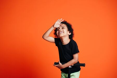 Little black boy covers his eyes with his hand looking into the distance and riding a scooter on an orange background