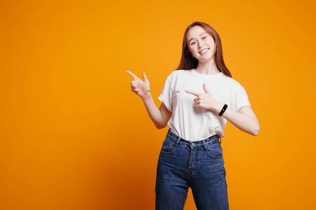 Girl with red hair in white T-shirt points her fingers to an empty space on the banner to insert her text on an orange background. Foto de archivo