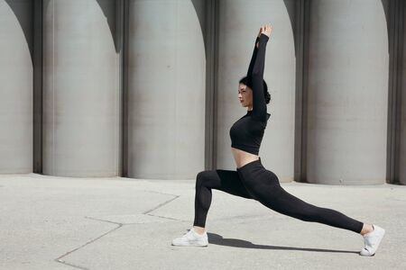 Profile of asian pilates trainer in black sportwear goes in for sports on street in park lunging forward and arms outstretched.