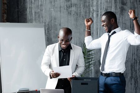 Dark-skinned businessman in white jacket happily looks at signed contract with investors, and black employee joyfully raises hands