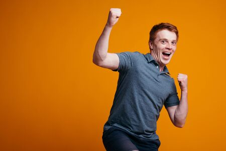 red-haired guy rejoices and waves his hands because of great joy and success in business. Discount banner for shops.