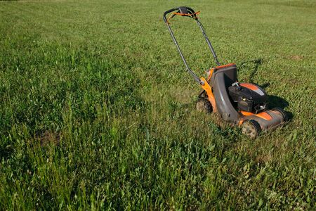 Photo of the process of cutting the lawn in the suburban area with the mower. Long lawn grass maintenance.