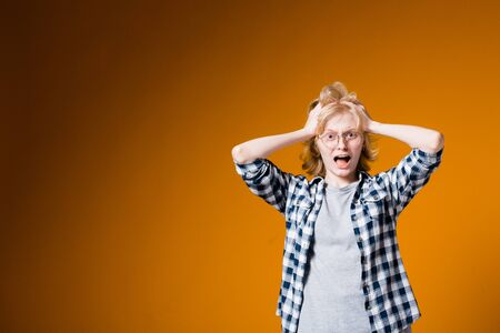 The young blonde girl in glasses in horror ruffles her hair from shock and unpleasant circumstances on an orange background in the studio