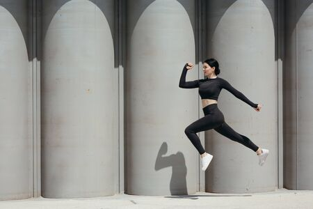 Photo of a sports Asian woman in a tight-fitting suit who froze sideways in a jump on the street against the background of concrete walls. Standard-Bild
