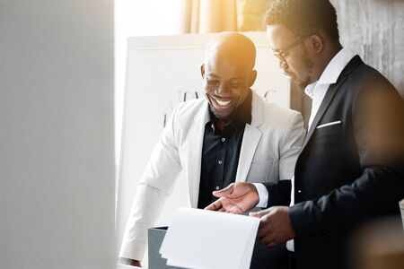 The black attorney shows documents to the Director in a white jacket while in the evening in the office