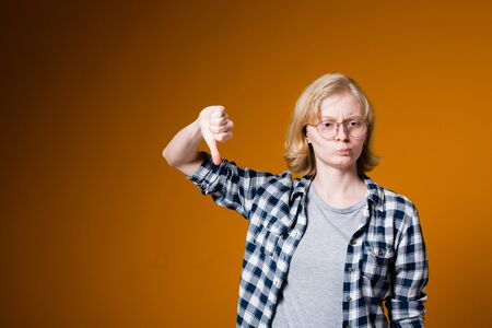 Distraught girl on a dark orange background. Blonde in checkered shirt looking at camera and showing thumbs down.