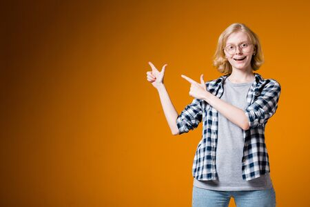The girl happily pointing in the upper left corner of the index finger. Cheerful girl in a shirt and glasses on a orange background.