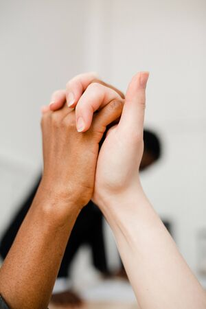 Vertical photo of The fight against racism. Two hands of different nationalities compress each other as a sign of support and solidarity.