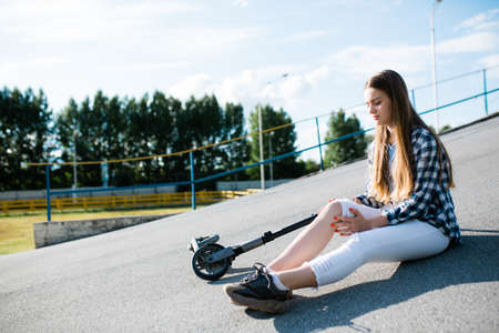A girl in white pants sits on the pavement and checks her knee for a bruise due to a fall on a scooter on the street. Sports street injuries 免版税图像 - 150587780