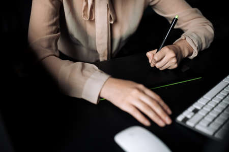 Close-up of female hand using graphics tablet, keyboard and mouse. Girl designer draws a sketch for a customer.