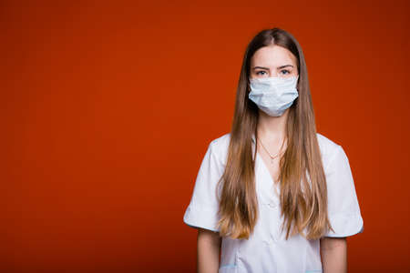 Portrait of a doctor girl in a medical mask with long hair and in a white coat on a red background