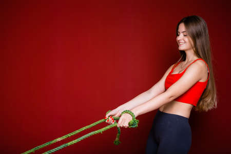 A young woman pulls two green ropes as a concept of severe social problems and discrimination against women on a red background 免版税图像