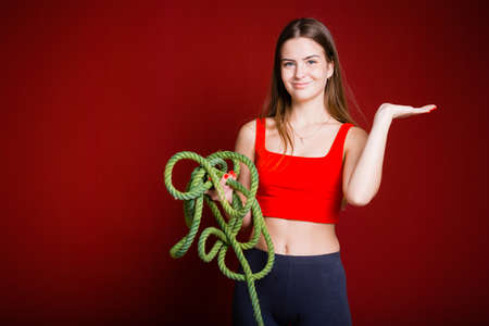 A girl with long hair holds a thick green rope in her hands and shows with her hand to the side on a red background