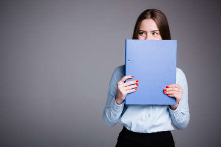 Business portrait of an office worker who is standing on a gray background and peeking out from behind a folder with documents in front of her