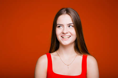 Female portrait of a girl in a red T-shirt who is looking at the camera and showing Like with her hand on an orange background