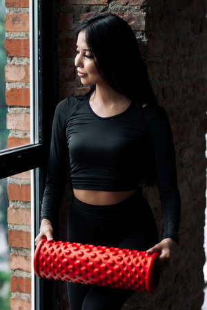 Vertical portrait of a girl in a black tight-fitting sportswear who stands near the window and holds a red massage cylinder.