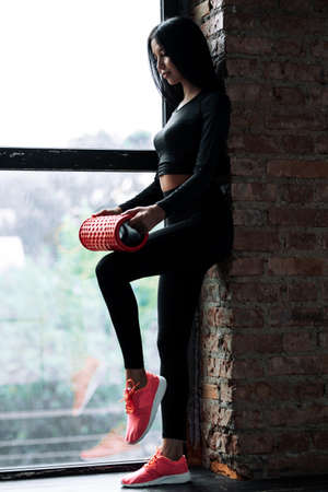Vertical photo of a girl in a black tight-fitting sportswear who stands near a window and mashes a quadriceps fascia with a massage cylinder.