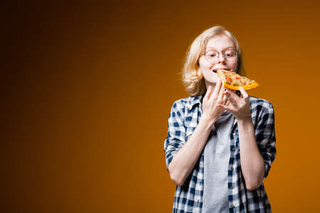 A Swedish girl with glasses and a plaid shirt brings a slice of pizza to her face to bite on an orange background.