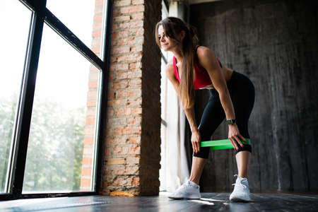 Profile view of a girl who protrudes her ass and leans forward to pull on an elastic green expander for further training