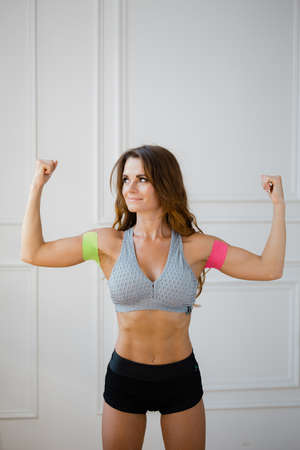 Sporty girl with kinesio tape on her arm. Fixation of the muscles of the biceps with a plaster for kinesitherapy