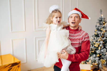 A man in a New Years hat with a child in his arms stands next to a New Year tree. Are surprised and look at the camera Stockfoto