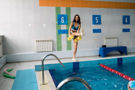 The girl the trainer in water aerobics shows an exercise with dumbbells for the pool. Sports, water sports