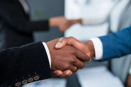 A close-up of two black men shaking hands. Investor and developer two African Americans shake hands.