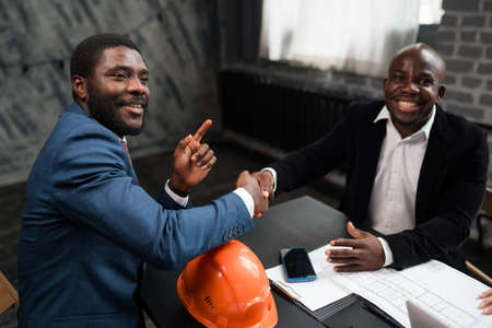 Two African Americans signed a cooperation agreement. Business investors shake hands. Orange construction hard hat on office desk Imagens