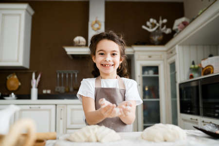 Portrait of a cute school-age girl with two pigtails, in a black chefs apron, who holds flour in her palms and sprinkles it on the dough